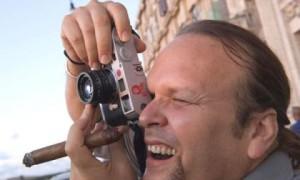 الكاميرة في يد والسيكار الكوبي في يد اخرى